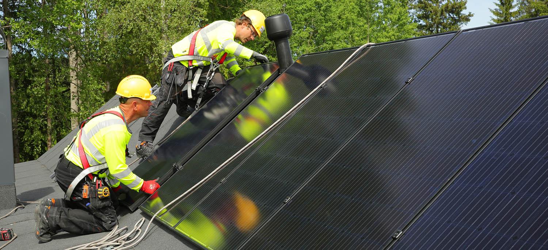 Playgreenin asentajat Aimar ja Indrek Sepp asensivat aurinkopaneelit Villa Elementin huopakatolle sen lappeen suuntaisesti.